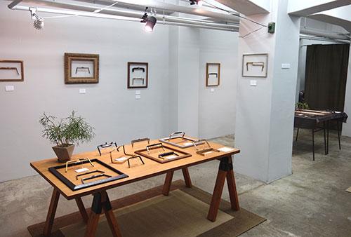 テーブルの上には昭和20~30年代の口金。当時はほとんどが真鍮製で、手彫りや腐食で透かし飾りを作るなどの手の込んだ細工が施されていた