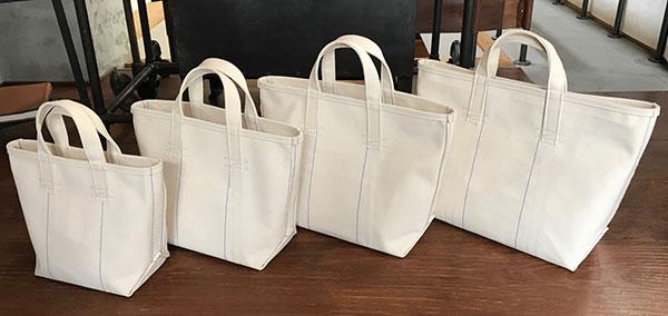 """アメリカのヴィンテージのコールマンバッグをモチーフにした4号生機のシャトル織トートバッグ。決して軽くはないが、しっかりとした厚みと丈夫な素材の鞄は、スロウのブランドコンセプトである""""時代に流されない良い物を""""という文言を体感できる。サイズも豊富に展開"""